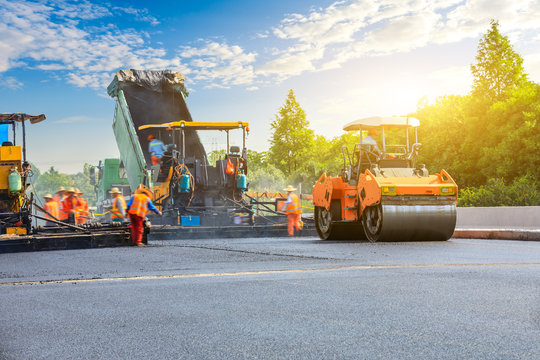 Construction site is laying new asphalt road pavement,road construction workers and road construction machinery scene.
