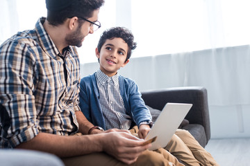 jewish father and smiling son using laptop in apartment