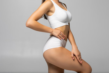 Obraz Close up shot of unrecognizable fit woman in lingerie isolated on white background. Torso of slim attractive female with flat belly in white underwear. Copy space for text. - fototapety do salonu