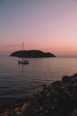 Seascape with moored sailing boat and island on background and with lavender bushes in the foreground at sunset. People have a nice time on the yacht. Maritime evening walk. Balearic islands, Majorca.