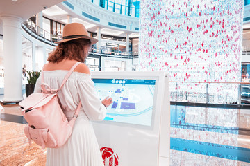 27 November 2019, UAE, Dubai: Happy asian girl using an interactive info touchscreen assistant in the shopping Mall