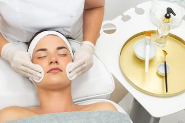Fototapeta Kosmetolog pielęgnuje twarz młodej kobiety. Pięlęgnacja twarzy.  obraz