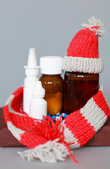 nose drops, nasal spray, cough syrup in a bottle of dark glass in a cap and scarf on a brown background