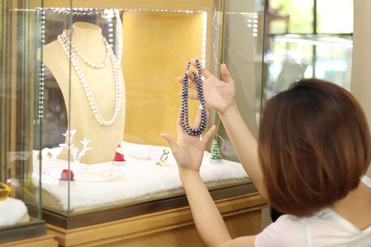 Asian short hair woman which is customer choosing and looking for jewellery gift for her special day with happy face. woman wearing beautiful Gems and diamond necklace in jewellery store