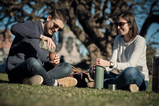 Young couple enjoying in the outdoor park drinking mate