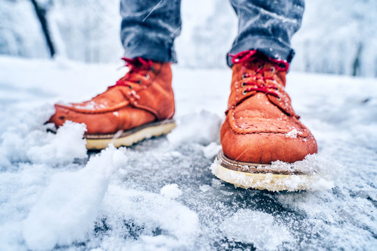 Feet of a man on a snowy sidewalk in brown boots. Winter slippery pawement. Seasonal weather concept