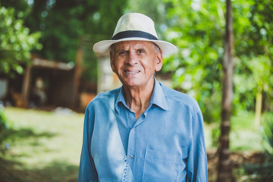 Portrait of smiling beautiful older male farmer. Elderly man at farm in summer day. Gardening activity. Brazilian elderly man.