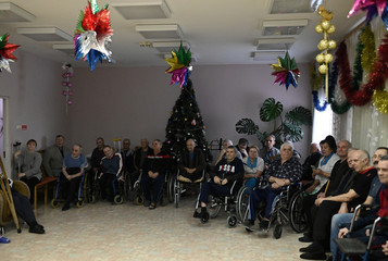 Residents and employees of a nursing home gather to watch a performance organized by volunteers on the occasion of the Christmas and New Year holidays in Omsk region