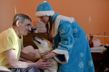 A volunteer assists a resident of a nursing home stroking a dog during a visit on the occasion of the Christmas and New Year holidays in Omsk region