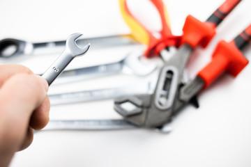 Fototapeta klucz płaski trzymany w dłoni, w tle zestaw narzędzi