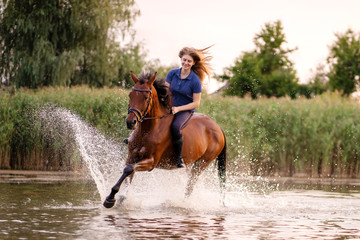 A young girl riding a horse on a shallow lake. A horse runs on water at sunset. Care and walk with the horse. Strength and Beauty Papier Peint