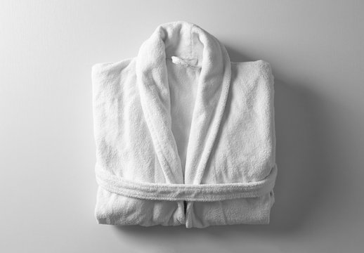 Clean folded bathrobe on white background, top view