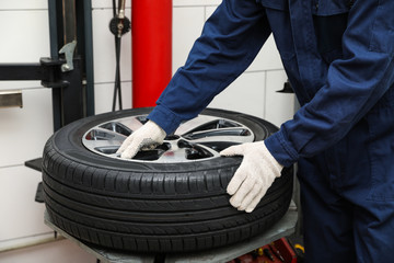 Man working with tire fitting machine at car service, closeup