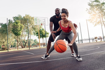 Outdoors Activity. African couple girl dribbling while guy defencing backdoor on basketball court smiling happy