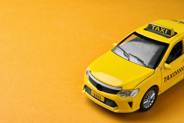 Yellow taxi car model on orange background. Space for text
