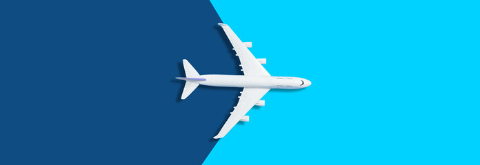 Flat lay design of travel concept with plane on blue background with copy space
