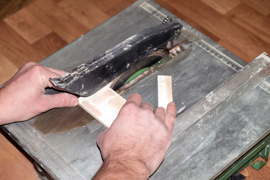 the process of cutting tile on a special tool with a diamond disk and wet sawing without dust. repair work performed by a specialist with a modern tool.