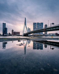Sunrise at Rotterdam, the Netherlands, relection of the skyline in a puddle after the rain