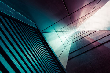 Abstract background. View through modern high rising skyscraper chimney upwards to blue sky with white clouds - abstract architecture detail background in turquoise teal blue to burgundy purple colors Fotomurales