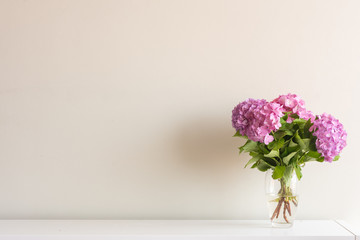 Pink hydrangea flowers with green leaves in glass vase on white side board against neutral wall background