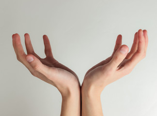 Female hands form a space for your text on a white background. Copy space