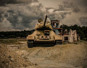 A war scene of the front side of a tank on a gravel hill aiming forward with a demolished house in the background