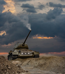 A war scene of a tank with a smoking turret under a dramatic sunset