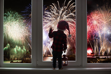 Toddler child standing in front of a big french doors, leaning against it looking at new years eve...
