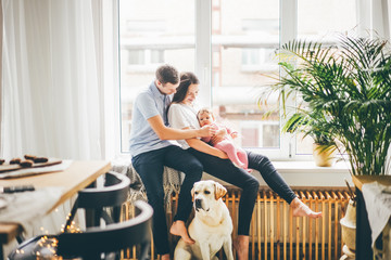 Family with daugther and dog sitting near the big window at the modern apartment. Wall mural