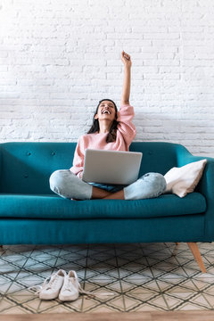 Pretty young woman celebrating something while using her laptop on the sofa at home.