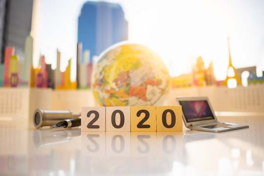 Miniature people: Wood block number 2020 with binoculars, laptop on blurred city scape using as background Choice of the best suited employee, HR, HRM, HRD, job recruiter concepts.
