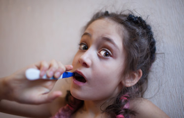 Little girl brushes her teeth with a toothbrush on a light background