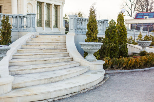 Luxury mansion with marble staircase, white stone balustrade and park garden. Large house of royal palace style