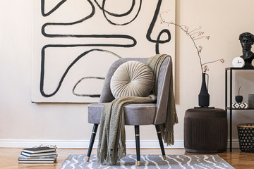 Interior design of living room with stylish gray armchair, abstract paintings on the wall, flowers...