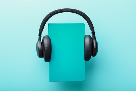 Headphones are worn on a book in a blue hardcover on a blue background, top view.