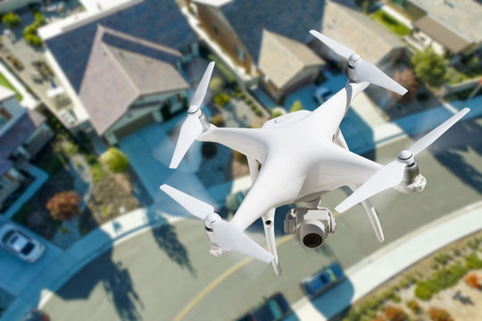 Unmanned Aircraft System Quadcopter Drone In The Air Over Residential Neighborhood