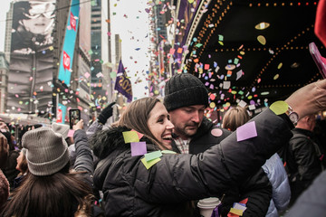 People take a picture of confetti as it's thrown from the Hard Rock Cafe marquee as part of the annual confetti test ahead of the New Year's Eve ball-drop celebrations in Times Square