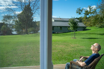 A retired man relaxes on backyard lawn in sunshine seen through glass window