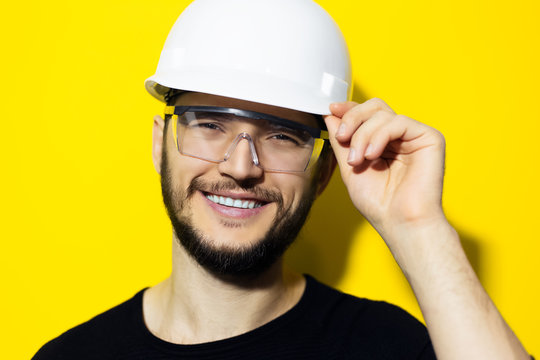 Studio portrait of young smiling man architect, builder engineer, wearing black sweater, touching his white construction safety helmet and glasses, isolated on yellow background.