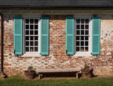 Simple blue shutters around white windows against a brick wall in colonial house in Virginia