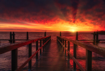 Foto auf Acrylglas Kastanienbraun wooden pier at sunrise on sea