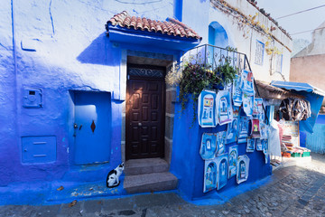 Foto op Aluminium Londen rode bus Traditional typical moroccan architectural details in Chefchaouen, Morocco, Africa Beautiful street of blue medina with blue walls and decorated with various objects (pots, jugs). A city with narrow,
