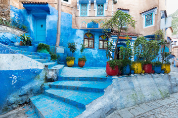 Deurstickers Traditional typical moroccan architectural details in Chefchaouen, Morocco, Africa Beautiful street of blue medina with blue walls and decorated with various objects (pots, jugs). A city with narrow,