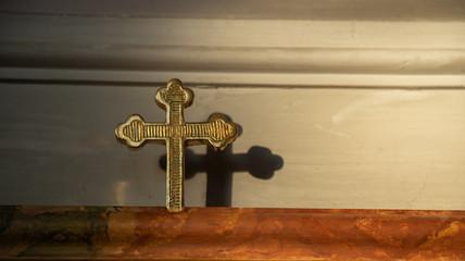 Goldenes Kreuz mit Schatten