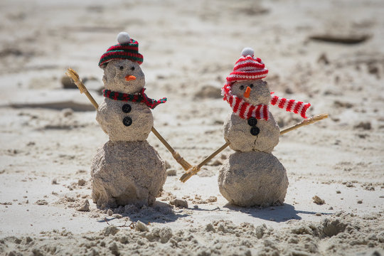 Two snowmen made out of sand on the beach