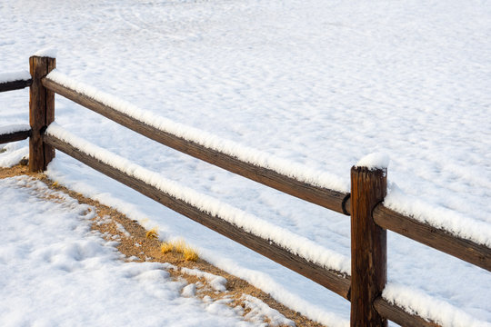 Corner wooden fence in rural setting with ground covered snow