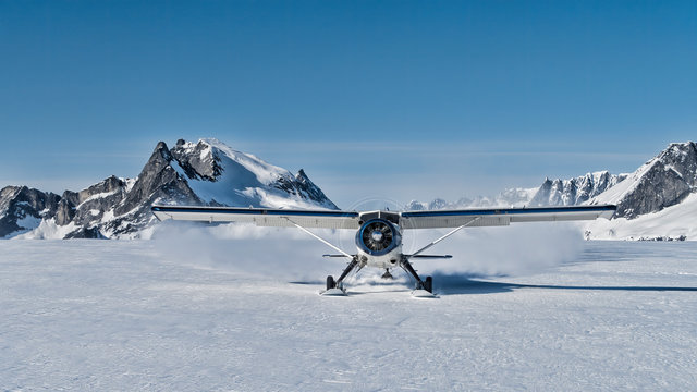 Small bush plane with skiis landing on an snow field