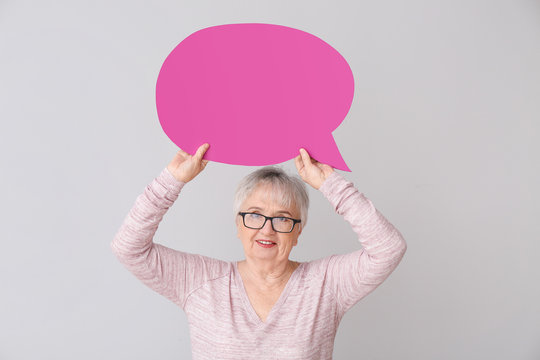 Senior woman with blank speech bubble on grey background