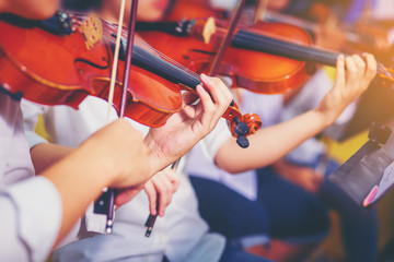 Musician is practicing violin in a music practice classroom prepare for performing violin stage. Concept of practicing violin for professional skills. Selected focus