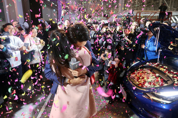 Tesla employee proposes to his girlfriend with a China-made Tesla Model 3 vehicle filled with flowers at a delivery ceremony in the Shanghai Gigafactory of the U.S. electric car maker in Shanghai